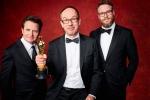 """William Goldenberg poses backstage with the Oscar for Achievement in film editing, for work on """"The Imitation Game"""" with Michael J. Fox and Seth Rogen"""
